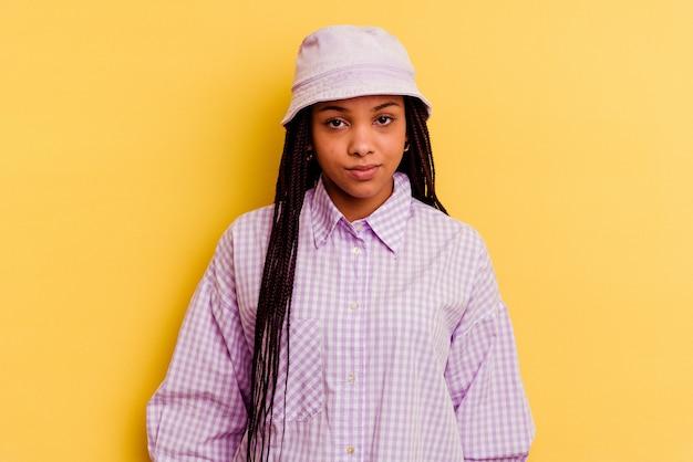 Giovane donna afroamericana isolata su sfondo giallo, faccia triste e seria, sentendosi infelice e scontenta