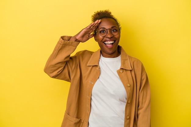 La giovane donna afroamericana isolata su fondo giallo grida forte, tiene gli occhi aperti e le mani tese.
