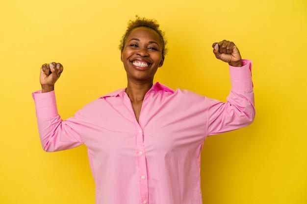 Giovane donna afroamericana isolata su sfondo giallo che mostra il gesto di forza con le braccia, simbolo del potere femminile