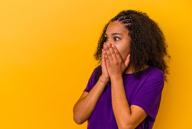 Giovane donna afroamericana isolata su sfondo giallo premuroso cercando di uno spazio di copia che copre la bocca con la mano.