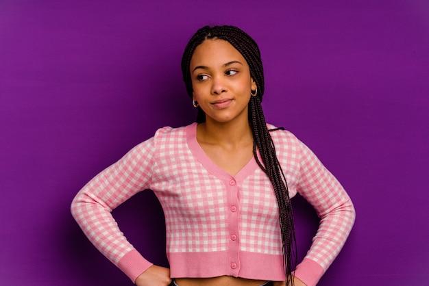 Giovane donna afroamericana isolata su giallo sognando di raggiungere obiettivi e scopi