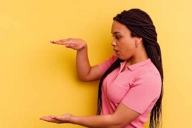 Giovane donna afroamericana isolata su giallo scioccata e stupita in possesso di uno spazio di copia tra le mani.