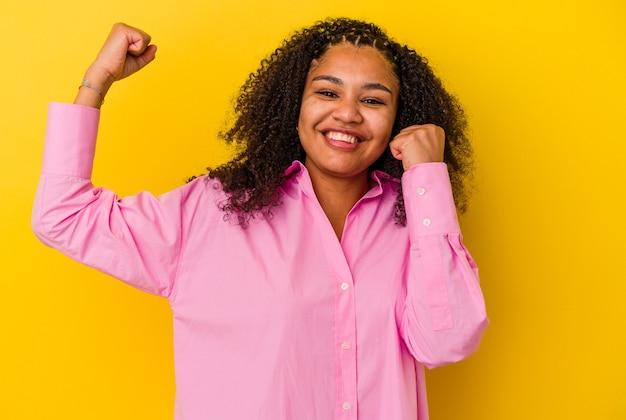Giovane donna afroamericana isolata sulla parete gialla ballando e divertendosi