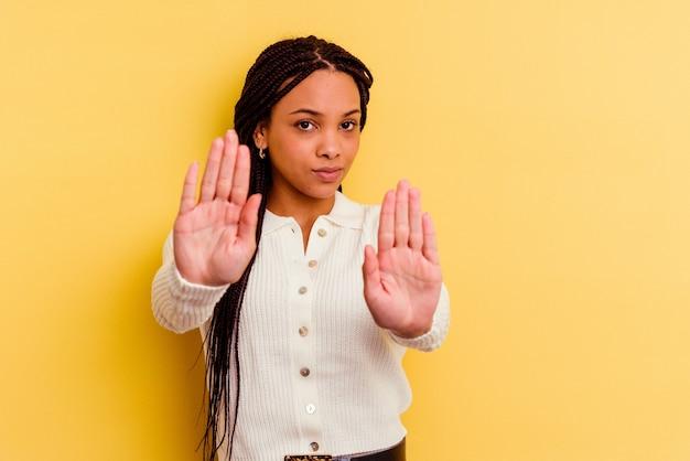 Giovane donna afroamericana isolata sul muro giallo in piedi con la mano tesa che mostra il segnale di stop, impedendoti