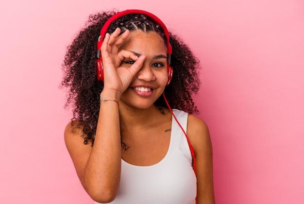 La giovane donna afroamericana che ascolta la musica con le cuffie isolate su fondo rosa ha eccitato mantenendo il gesto giusto sull'occhio