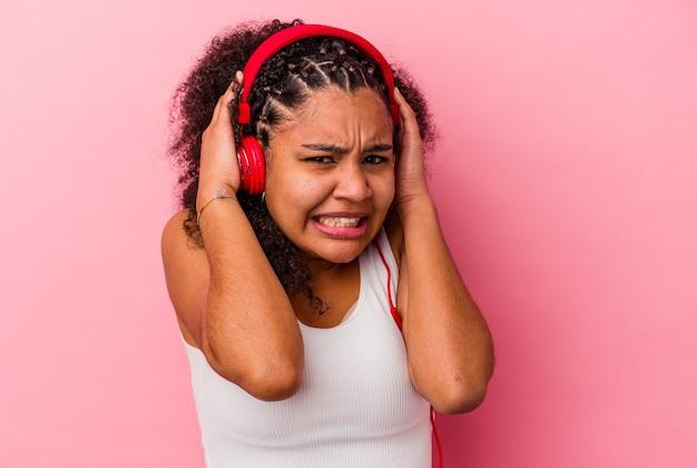 Giovane donna afroamericana che ascolta la musica con le cuffie isolate sul muro rosa che copre le orecchie con le mani.