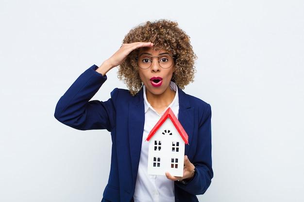 Giovane donna afroamericana che sembra felice, stupita e sorpresa, sorridente e realizzando incredibili e incredibili buone notizie con il modello di casa