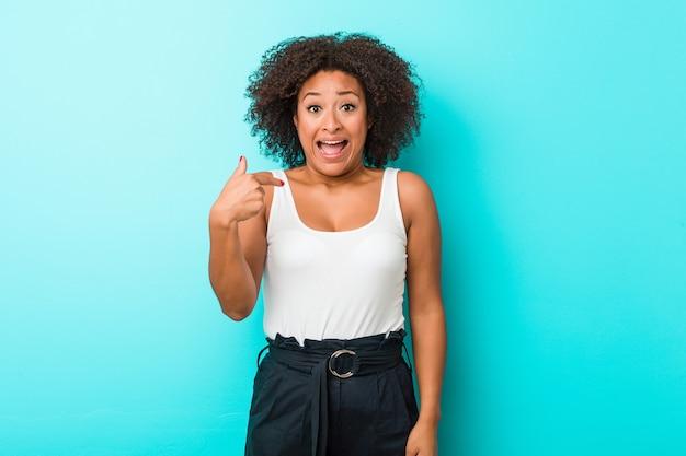 Persona di giovane donna afroamericana che punta a mano uno spazio di copia della camicia, orgoglioso e fiducioso