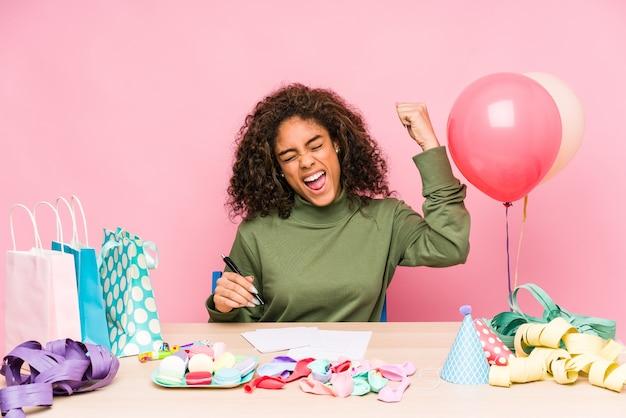 Giovane donna afroamericana che pianifica un compleanno che solleva il pugno dopo una vittoria, concetto del vincitore.