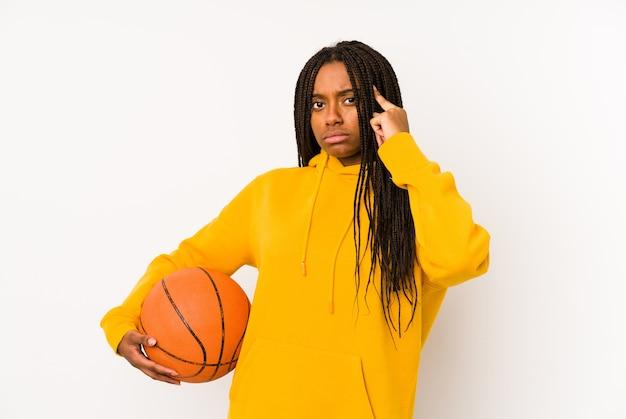 Giovane donna afroamericana che gioca a basket isolato tempio di puntamento con il dito, pensando, concentrato su un compito.