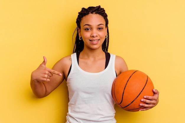 Giovane donna afroamericana che gioca a basket isolata sulla persona gialla che punta a mano uno spazio di copia della maglietta, orgogliosa e sicura