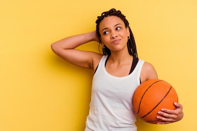 Giovane donna afro-americana che gioca a basket isolato sulla parete gialla che tocca la parte posteriore della testa, pensando e facendo una scelta.