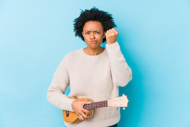 Giovane donna afro-americana che gioca ukelele isolato mostrando pugno aggressivo espressione facciale.