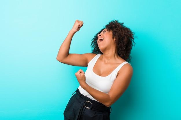 Giovane donna afroamericana che alza il pugno dopo una vittoria, concetto del vincitore.