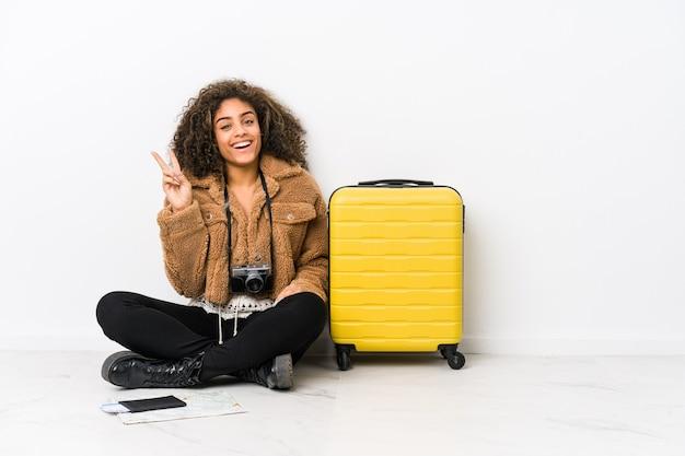 Giovane donna afroamericana pronta per un viaggio gioioso e spensierato che mostra un simbolo di pace con le dita.