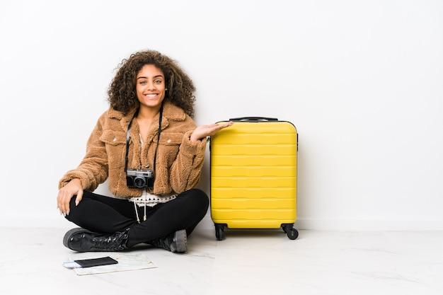 Giovane donna afroamericana pronta per un viaggio che mostra uno spazio di copia su una palma e che tiene un'altra mano sulla vita.