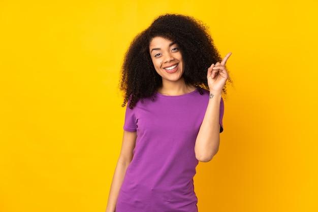 Giovane donna afroamericana che mostra e solleva un dito in segno del meglio