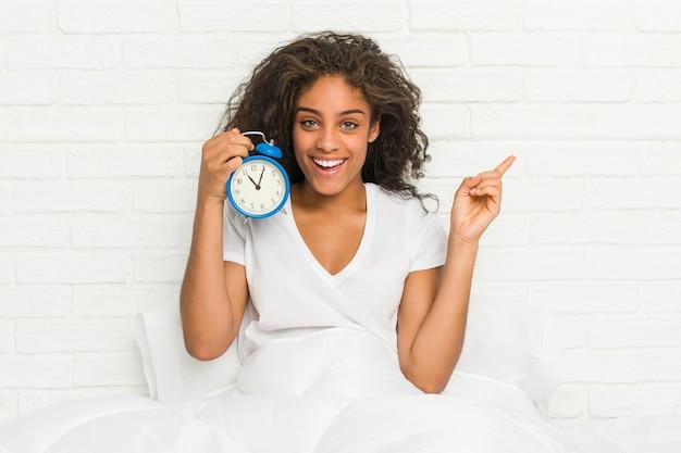 Giovane donna afroamericana seduta sul letto con in mano una sveglia sorridendo allegramente indicando con l'indice di distanza.