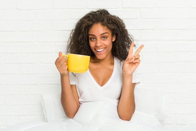 Giovane donna afroamericana che si siede sul letto che tiene una tazza da caffè che mostra numero due con le dita.