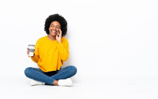 Giovane donna afroamericana che si siede sul pavimento che tiene caffè da portare via e un cellulare