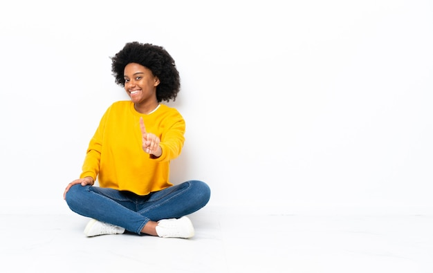 Giovane donna afro-americana seduta sul pavimento mostrando e alzando un dito