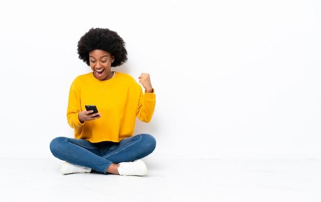 Giovane donna afroamericana che si siede sul pavimento sorpresa e che invia un messaggio
