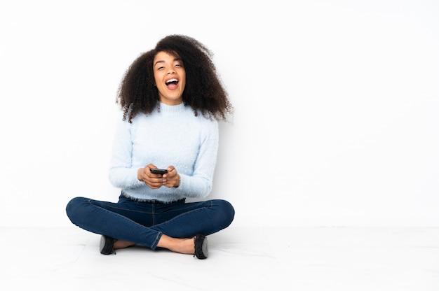 La giovane donna afroamericana che si siede sul pavimento ha sorpreso e che invia un messaggio