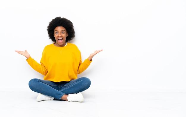 Giovane donna afro-americana seduta sul pavimento con l'espressione del viso scioccata