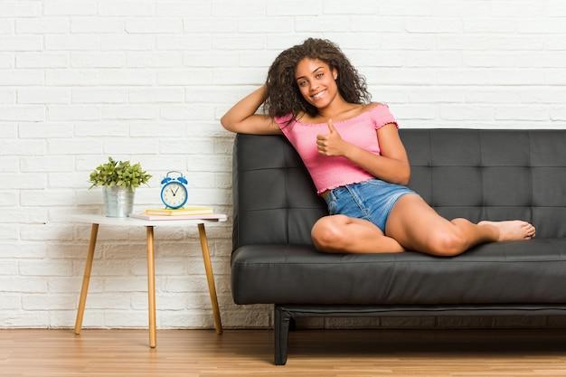 Giovane donna afroamericana seduta sul divano sorridendo e alzando il pollice