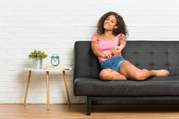 Giovane donna afroamericana seduta sul divano che allunga le braccia, posizione rilassata.