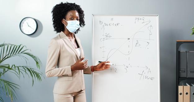 Insegnante di giovane donna afroamericana in maschera medica in piedi a bordo in aula e raccontando le leggi di fisica o geometria alla classe. concetto di pandemia. scuola durante il coronavirus. lezione educativa.