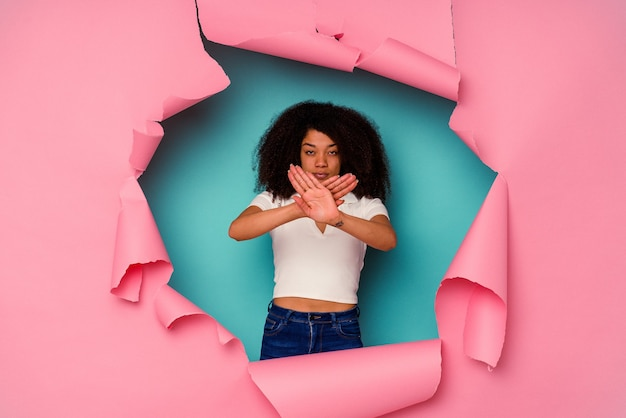 Giovane donna afroamericana in carta strappata isolata su sfondo blu che fa un gesto di rifiuto