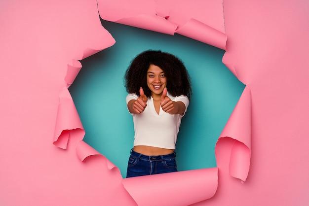 Giovane donna afroamericana in carta strappata isolata su sfondo blu con pollice in alto, acclamazioni per qualcosa, concetto di supporto e rispetto.