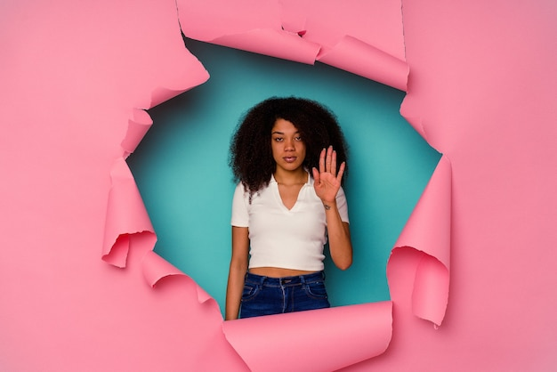 Giovane donna afroamericana in carta strappata isolata su blu in piedi con la mano tesa che mostra il segnale di stop, impedendoti.