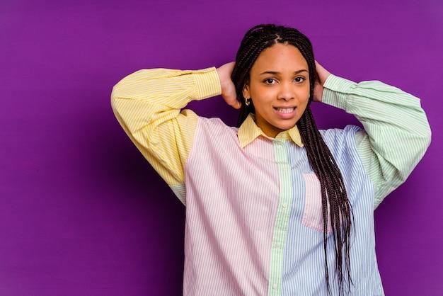 Giovane donna afroamericana che tocca la parte posteriore della testa, pensando e facendo una scelta.