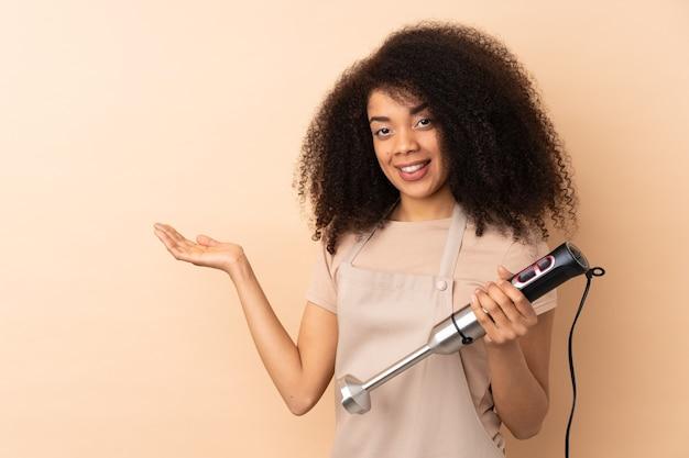 Giovane donna afroamericana utilizzando frullatore a immersione isolato su beige che estende le mani a lato per invitare a venire