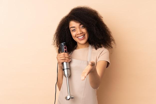 Giovane donna afroamericana che usando il miscelatore della mano isolato sulla stretta di mano beige dopo il buon affare
