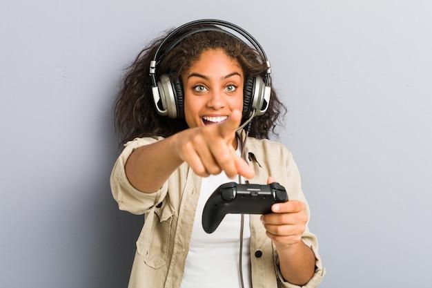 Giovane donna afroamericana utilizzando le cuffie e il controller di gioco