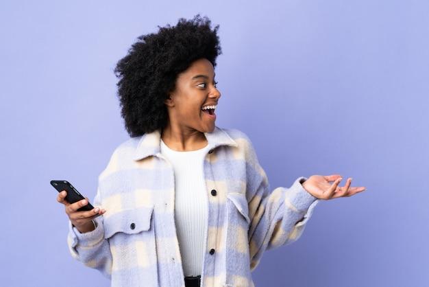 Giovane donna afroamericana che per mezzo del telefono cellulare isolato su fondo porpora con espressione facciale di sorpresa