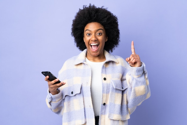 Giovane donna afroamericana utilizzando il telefono cellulare isolato