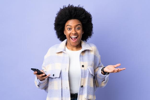 Giovane donna afroamericana che per mezzo del telefono cellulare sulla parete porpora con espressione facciale colpita