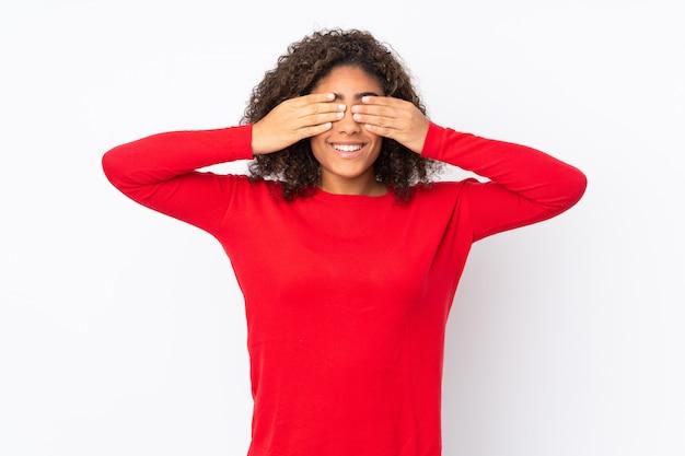 La giovane donna afroamericana sul rivestimento della parete osserva a mano e sorridendo
