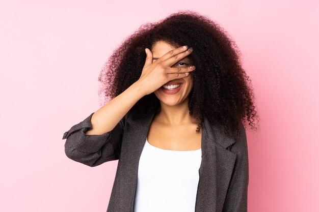 La giovane donna afroamericana sopra il rivestimento murale osserva a mano e sorridendo