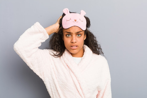 Giovane donna afroamericana che indossa un pigiama e una maschera per dormire scioccata, ha ricordato un incontro importante.
