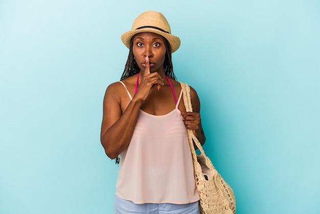 Giovane donna afroamericana che indossa abiti estivi isolati su sfondo blu mantenendo un segreto o chiedendo silenzio.