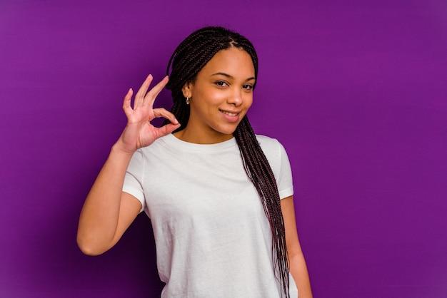 La giovane donna afroamericana ammicca un occhio e tiene un gesto giusto con la mano.