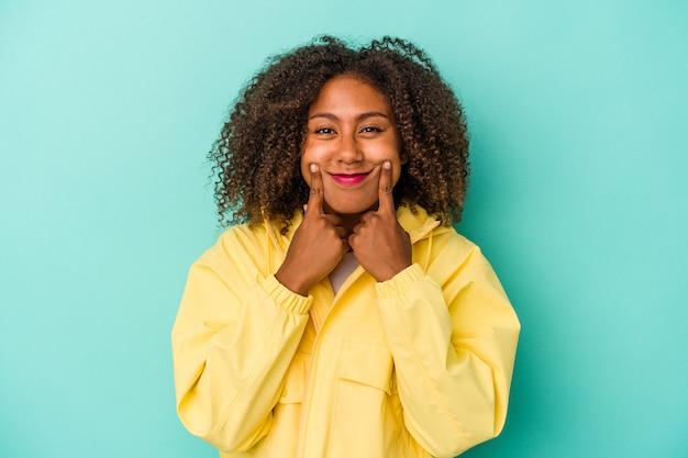 Giovane donna afroamericana con capelli ricci isolata su fondo blu che dubita tra due opzioni.