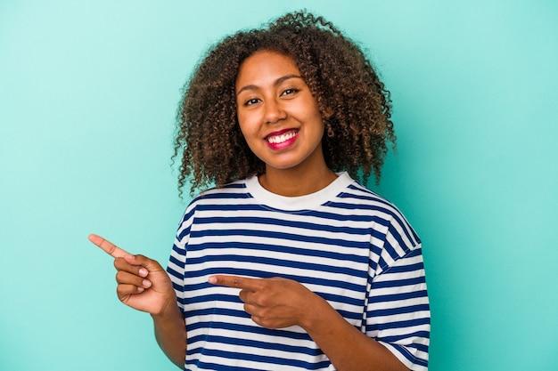 La giovane donna afroamericana con capelli ricci isolata su fondo blu ha eccitato indicando con gli indici via.