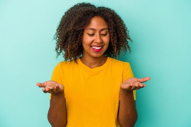 Giovane donna afroamericana con capelli ricci isolata su fondo blu che tiene qualcosa con le palme, offrendo alla macchina fotografica.