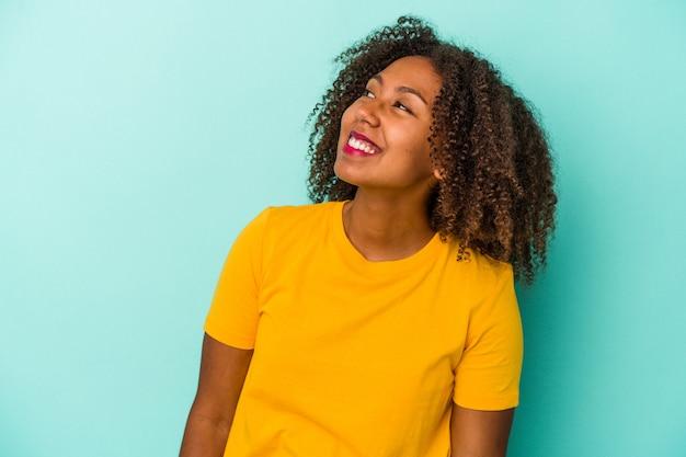 Giovane donna afroamericana con capelli ricci isolati su sfondo blu risata rilassata e felice, collo allungato che mostra i denti.